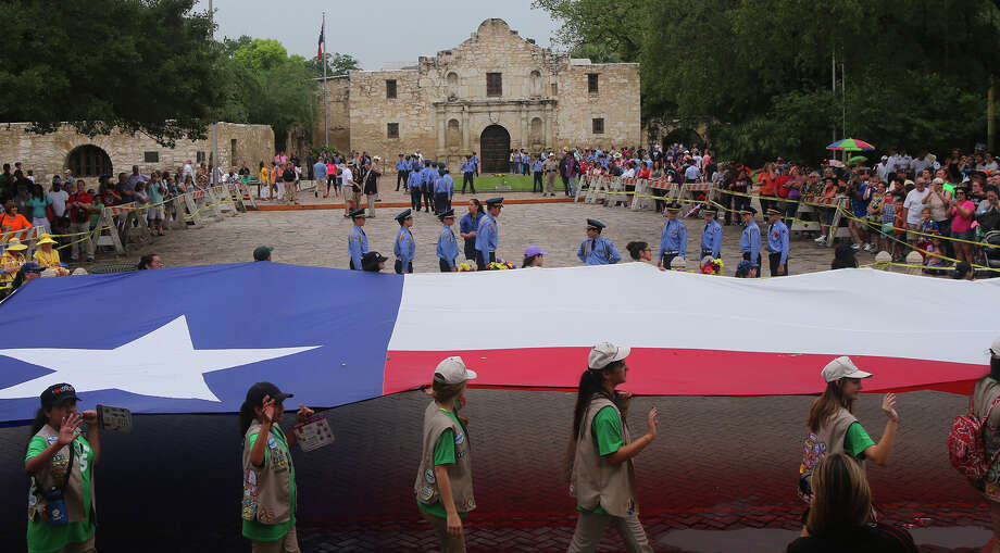 Girl Scouts carry the Texas flag past the Alamo on Friday during the Battle of Flowers Parade, which dates back to 1891. Photo: John Davenport / San Antonio Express-News / ©San Antonio Express-News/John Davenport