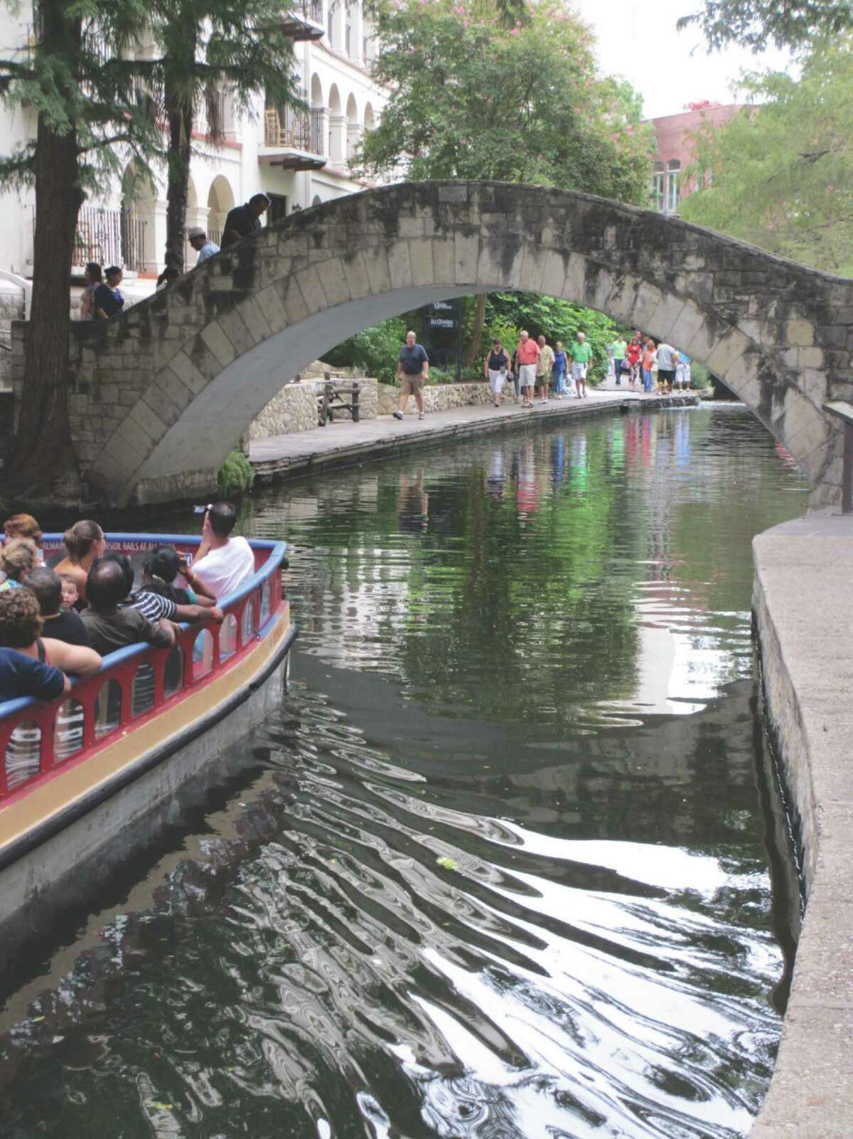 If locals can sometimes seem jaded with their world-famous River Walk, tourists see it as an enchanting, must-see-and-visit site. Sightseeers (above) take a barge ride while others explore its sidewalks and bridges.