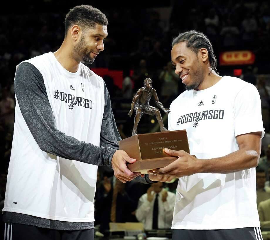San Antonio Spurs' Tim Duncan gives teammate Kawhi Leonard the NBA Defensive Player of the Year trophy before the start of the game against the Los Angeles Clippers of Game 3 in the Western Conference playoffs Friday April 24, 2015 at the AT&T Center. Photo: Edward A. Ornelas /San Antonio Express-News / © 2015 San Antonio Express-News