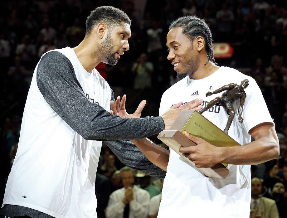 San Antonio Spurs' Tim Duncan gives teammate Kawhi Leonard the NBA Defensive Player of the Year trophy before the start of the game against the Los Angeles Clippers of Game 3 in the Western Conference playoffs Friday April 24, 2015 at the AT&T Center. Photo: Edward A. Ornelas, Staff / San Antonio Express-News / © 2015 San Antonio Express-News
