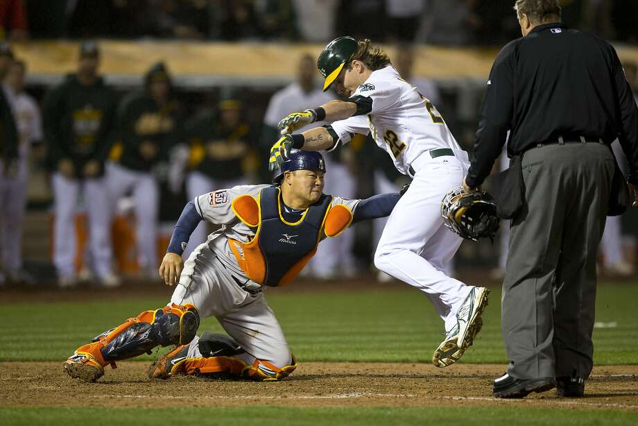 Josh Reddick, who doubled home two runs, is tagged by Hank Conger while trying to score on an errant throw to the plate. Photo: Jason O. Watson, Getty Images