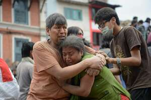 A Nepalese man and woman hold each other in Kathmandu's Durbar Square, a UNESCO World Heritage Site that was severely damaged by an earthquake on April 25, 2015. A massive 7.8 magnitude earthquake killed hundreds of people April 25 as it ripped through large parts of Nepal, toppling office blocks and towers in Kathmandu and triggering a deadly avalanche that hit Everest base camp. AFP PHOTO / PRAKASH MATHEMAPRAKASH MATHEMA/AFP/Getty Images