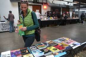 Sarah Koster shops for books sold by Manic D Press publishers at the 20th annual Bay Area Anarchist Book Fair in Oakland, Calif. on Saturday, April 25, 2015.