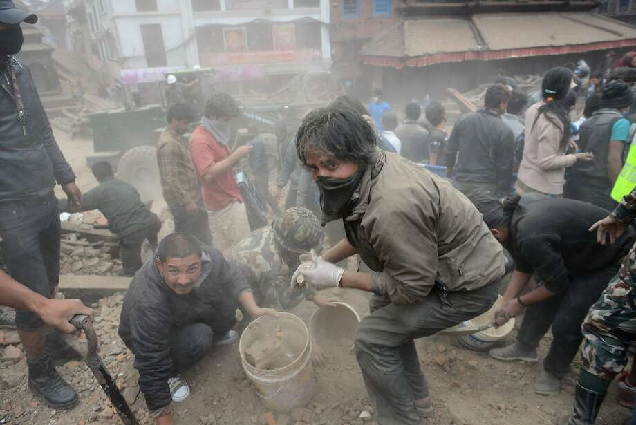 TOPSHOTS People clear rubble in Kathmandu's Durbar Square, a UNESCO World Heritage Site that was severely damaged by an earthquake on April 25, 2015. A massive 7.8 magnitude earthquake killed hundreds of people April 25 as it ripped through large parts of Nepal, toppling office blocks and towers in Kathmandu and triggering a deadly avalanche that hit Everest base camp. AFP PHOTO / PRAKASH MATHEMAPRAKASH MATHEMA/AFP/Getty Images Photo: Prakash Mathema, AFP / Getty Images