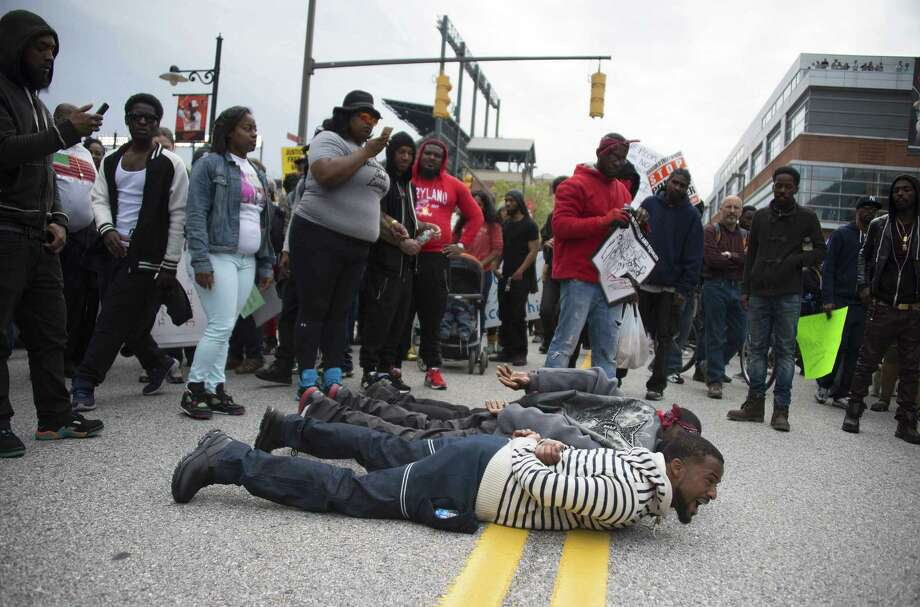 Demonstrators lie on the street as others march to protest the death of Freddie Gray in Baltimore. Photo: Jim Watson /Getty Images / AFP