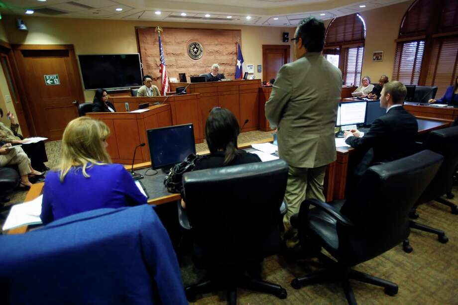 """The mother of two children, second from left, listens Wednesday March 11, 2015 to her attorney speak during a hearing in Judge Richard Garcia's courtroom. Judge Peter Sakai is overseeing a """"redesign"""" of Children's Court, which deals with families that have entered CPS system. Begun two months ago, the redesign models off of Family Drug Court, where parents are innundated with services to overcome addiction and to keep or get their kids back, and the approach is far less adversarial than traditional CC. The goal is to safely reunify more kids with familes that have gone through CPS, to empower families instead of punish them and keep more families intact Photo: William Luther, Staff / San Antonio Express-News / © 2015 San Antonio Express-News"""