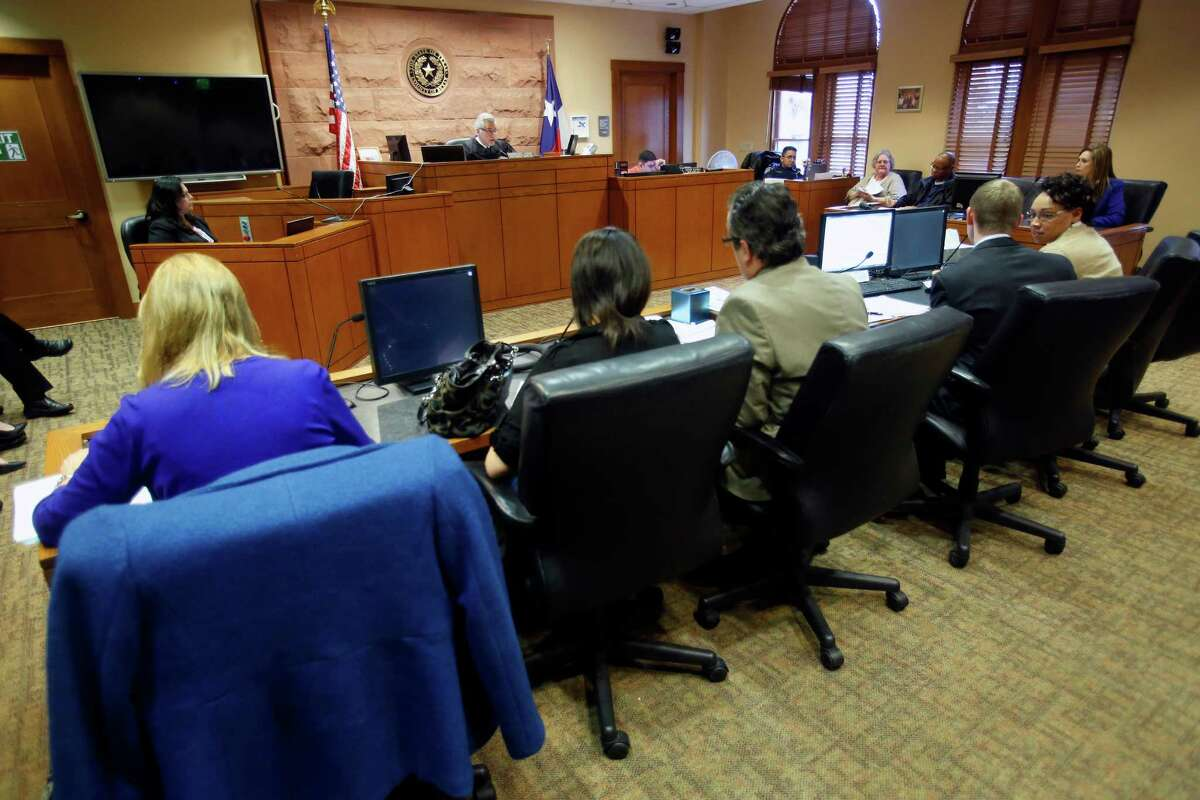 """The mother of two children, second from left, sits in court Wednesday March 11, 2015 during a hearing in Judge Richard Garcia's courtroom. Judge Peter Sakai is overseeing a """"redesign"""" of Children's Court, which deals with families that have entered CPS system. Begun two months ago, the redesign models off of Family Drug Court, where parents are innundated with services to overcome addiction and to keep or get their kids back, and the approach is far less adversarial than traditional CC. The goal is to safely reunify more kids with familes that have gone through CPS, to empower families instead of punish them and keep more families intact"""