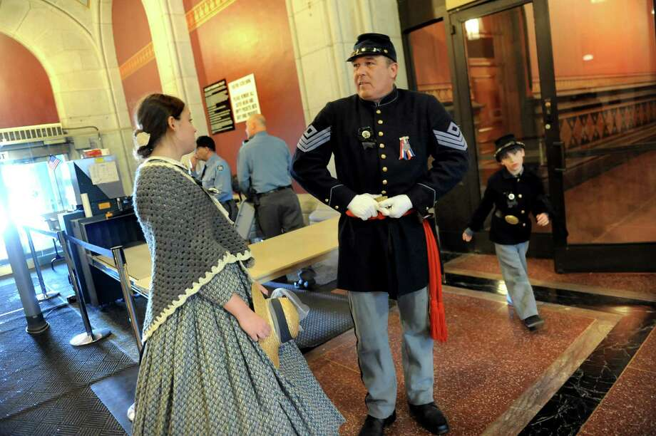 Re-enactor David Otto of Wilton, center, puts himself back together after going through security on Saturday, April 25, 2015, at the Capitol in Albany, N.Y. Otto joins his daughter Lily Otto, 17, left, and Henry Otto, 7, to take part in the re-enactment of President Lincoln's funeral train stop in Albany. (Cindy Schultz / Times Union) Photo: Cindy Schultz / 00031417A