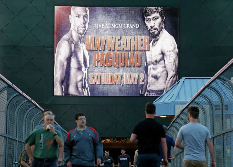 People walk across a footbridge by a sign advertising the boxing bout between Floyd Mayweather Jr. and Manny Pacquiao, Wednesday, April 22, 2015, in Las Vegas. (AP Photo/John Locher) Photo: John Locher, STF / Associated Press / AP