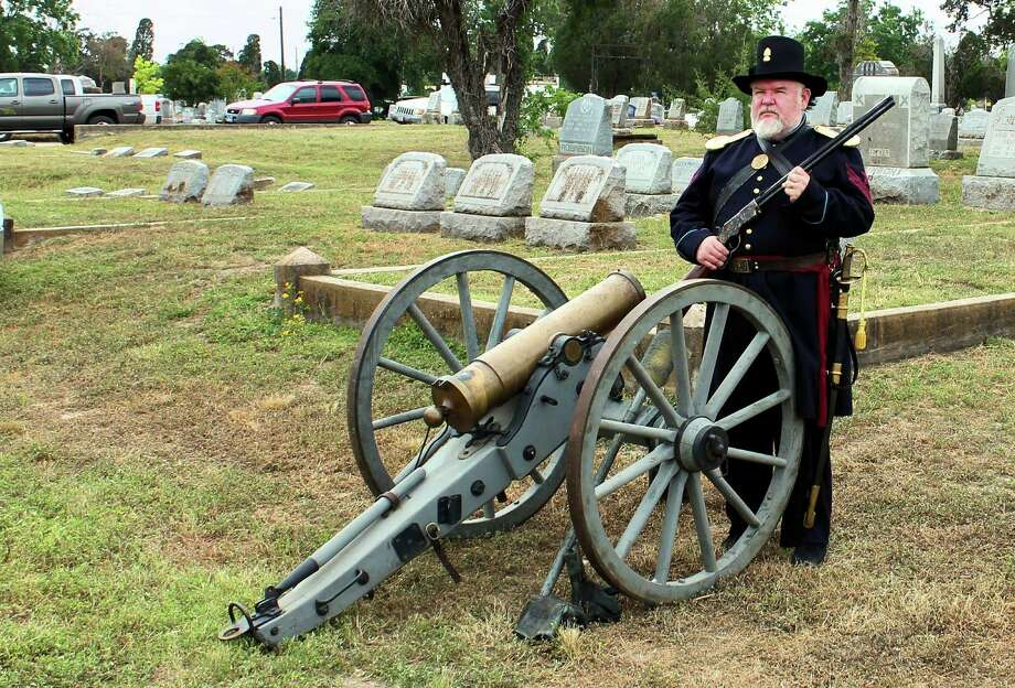 "A historical actory poses with a gun and canon during Confederate Decoration Day, which has been observed in San Antonio since the late 19th century. The group is involved in historic preservation of the old Confederate Cemetery in the East Side complex of city cemeteries, where Confederate Veterans were buried. The women in black are ""Black Roses,""; members of the Order of the Confederate Rose who portray mourners of fallen Confederates at memorial services. Photo: /Courtesy Of The Confederate Cemetery"