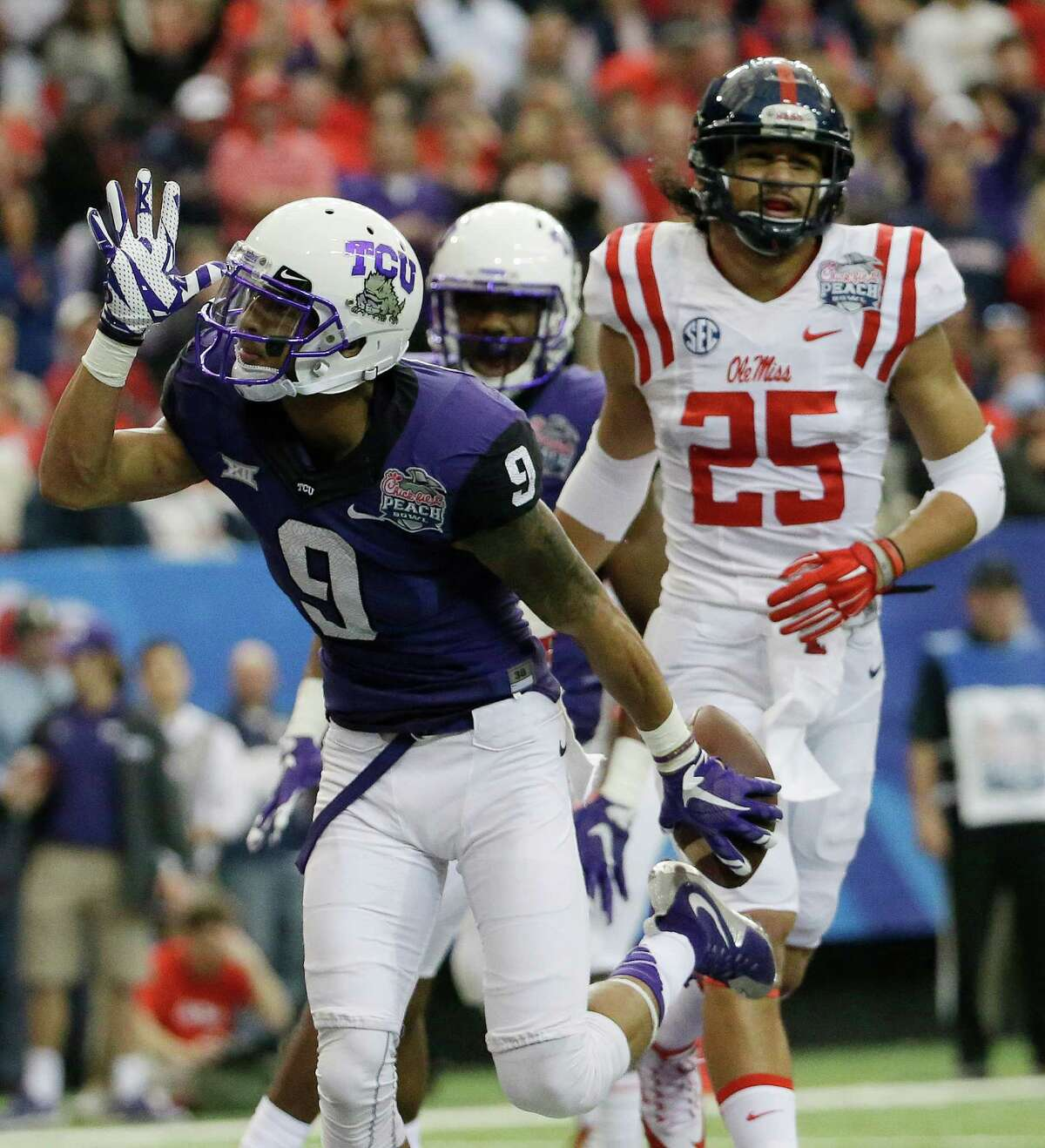 """TCU wide receiver Josh Doctson (9) makes the """"land shark"""" sign after his touchdown against Mississippi during the first half of the Peach Bowl NCAA on Dec. 31, 2014, in Atlanta."""