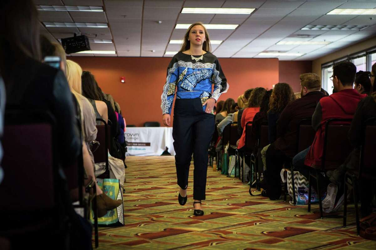A model wearing designs by Seattle Pacific University student Anna Ardill, walks the runway during the Fashion Industry Conference hosted by Sanford-Brown College on Saturday, April 25, 2015. Ardill said she created her three outfits with fabric she brought from Nigeria, which helped inspire each of her designs. The event, held to expose high school students to the fashion industry, included workshops, a fashion show and industry experts.