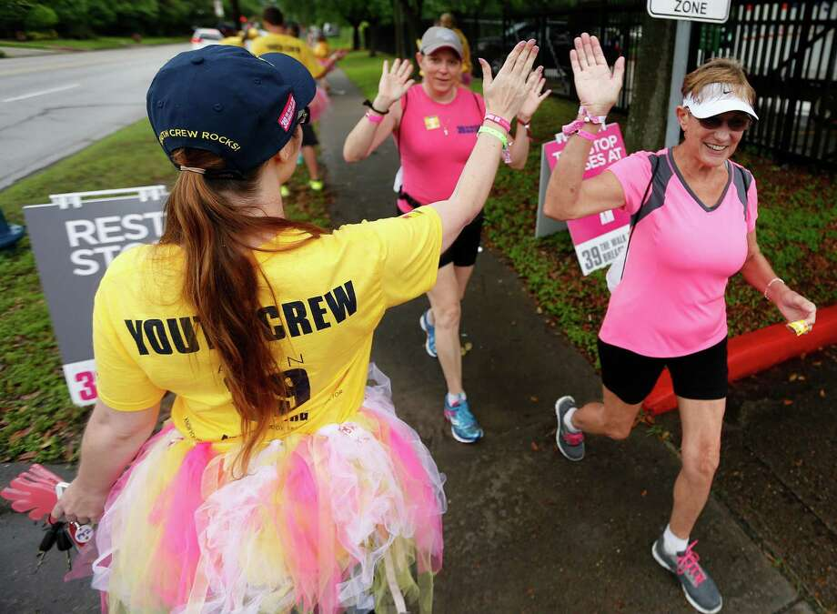 "Members of the ""Youth Crew"" cheer on walkers at a rest station on San Felipe during the AVON 39 The Walk to End Breast Cancer, formerly known as the Avon Walk for Breast Cancer, Saturday, April 25, 2015, in Houston.  AVON 39 Houston, the first of seven walks across the country, began with a 26.2 mile walk through the Houston area. Participants will spend Saturday night at Rice University, sleeping in pink two-person tents. The walk continues Sunday with a 13.1 mile walk to the closing ceremonies at Stude Park. Photo: Karen Warren, Houston Chronicle / © 2015 Houston Chronicle"