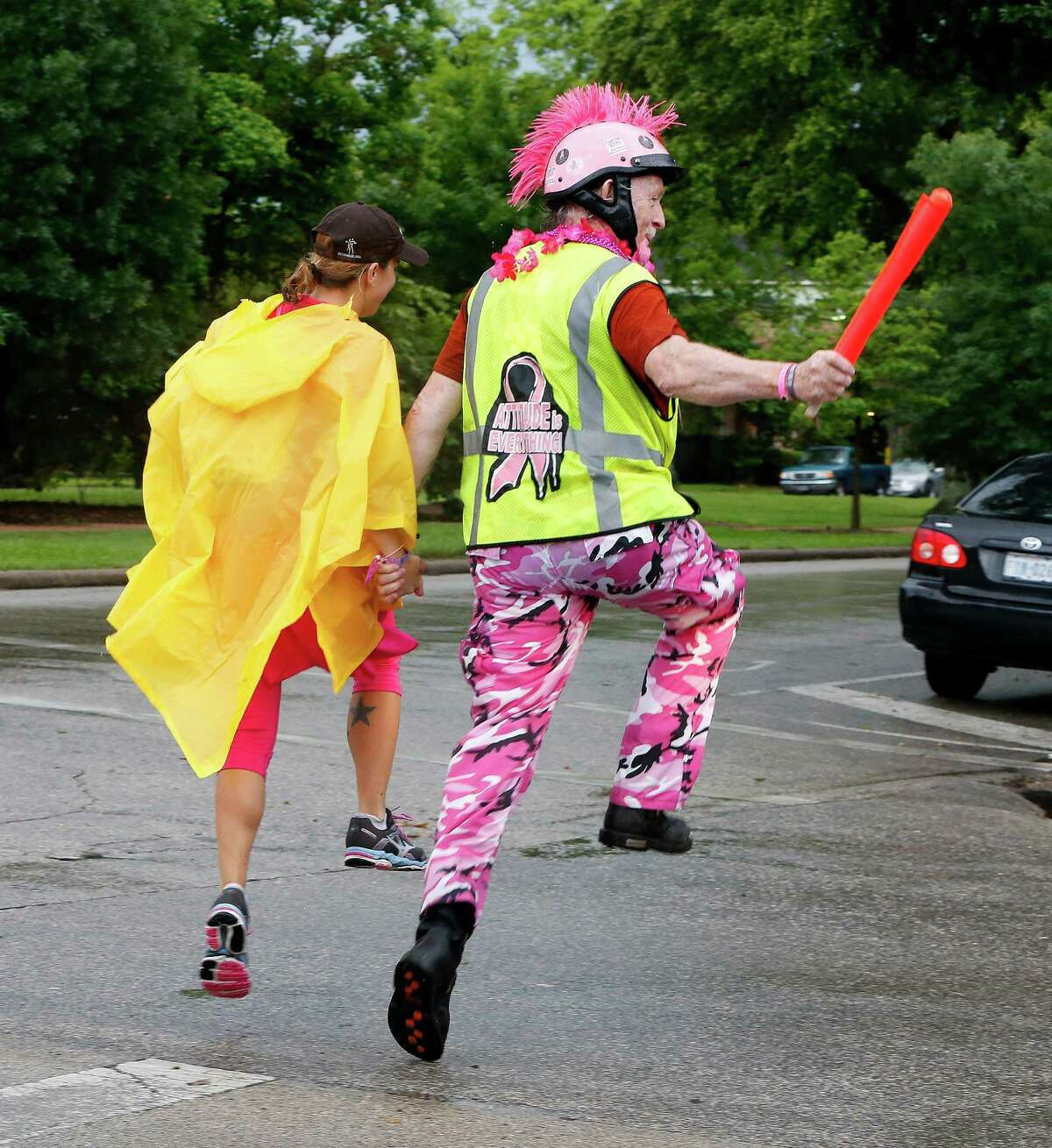 Ralph Walters, a motorcycle safety crew member, skips across an intersection with a walker during the AVON 39 The Walk to End Breast Cancer.