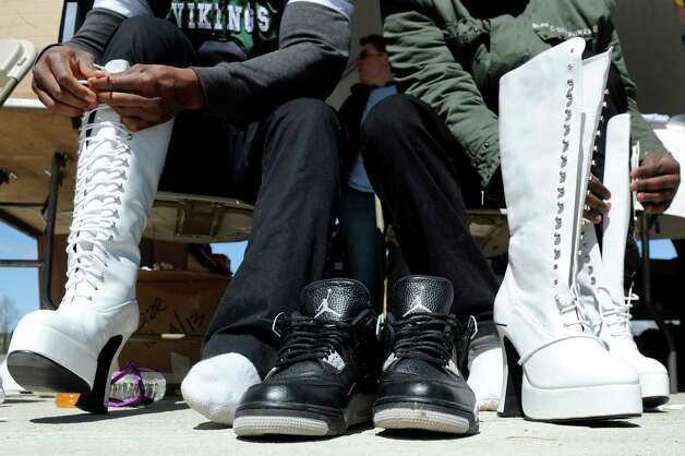 Hudson Valley Community College students Shemneil Brown, 20, left, and Xavier Miller, 22, trade up their sneakers for tall, lace-up boots during Walk a Mile in Her Shoes on Saturday, April 25, 2015, at Riverfront Park in Troy, N.Y. The event is a playful opportunity for men to raise their voices against sexual violence. (Cindy Schultz / Times Union) Photo: Cindy Schultz / 00031587A