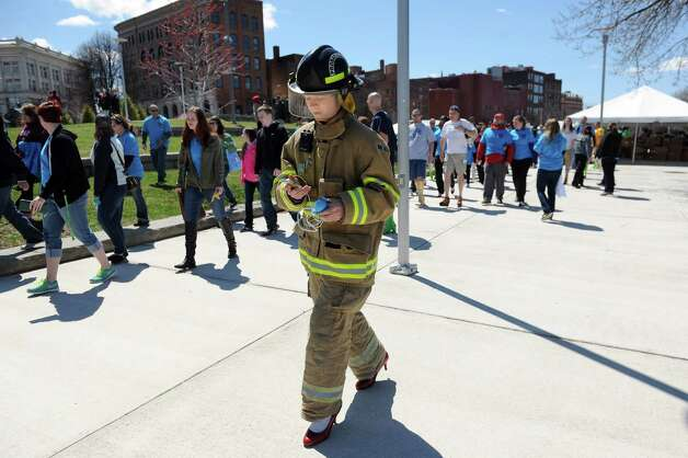 Zach Eaton, 17, a Whitehall volunteer firefighter, center, wears red pumps with his fire suit during Walk a Mile in Her Shoes on Saturday, April 25, 2015, at Riverfront Park in Troy, N.Y. Eaton arrived with 65 students from Whitehall High School for the walk. The event is a playful opportunity for men to raise their voices against sexual violence. (Cindy Schultz / Times Union) Photo: Cindy Schultz / 00031587A