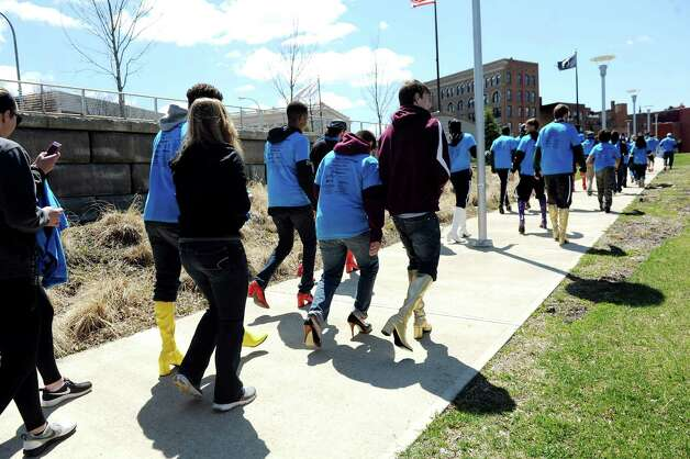 Families and friends walk with men in high heels during Walk a Mile in Her Shoes on Saturday, April 25, 2015, at Riverfront Park in Troy, N.Y. The event is a playful opportunity for men to raise their voices against sexual violence. (Cindy Schultz / Times Union) Photo: Cindy Schultz / 00031587A