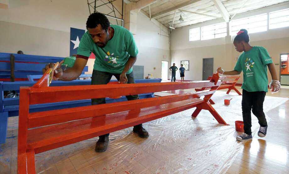 "George Clay, left, and Nicky'Anna Miles, 7, paint benches during the 14th annual ""Comcast Cares Day"" at the Holthouse Boys and Girls Club on Canal Street, Saturday, April 25, 2015, in Houston. More than 3,000 local Comcast NBCUniversal employees and their friends and families volunteered on Saturday to provide hands-on help at 11 different locations around Greater Houston, including the Houston Food Bank. Photo: Karen Warren, Houston Chronicle / © 2015 Houston Chronicle"