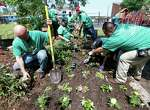 "Comcast employees plant flowers in a flower garden during the 14th annual ""Comcast Cares Day"" at the Holthouse Boys and Girls Club on Canal Street, Saturday, April 25, 2015, in Houston."