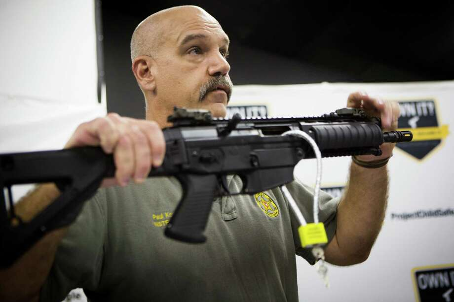 Paul Kowalik, an instructor from the Harris County Constable Precinct 4, shows a weapon secured with a lock during a firearm safety presentation, Saturday, April 25, 2015, in North Houston. Photo: Marie D. De Jesus, Houston Chronicle / © 2015 Houston Chronicle
