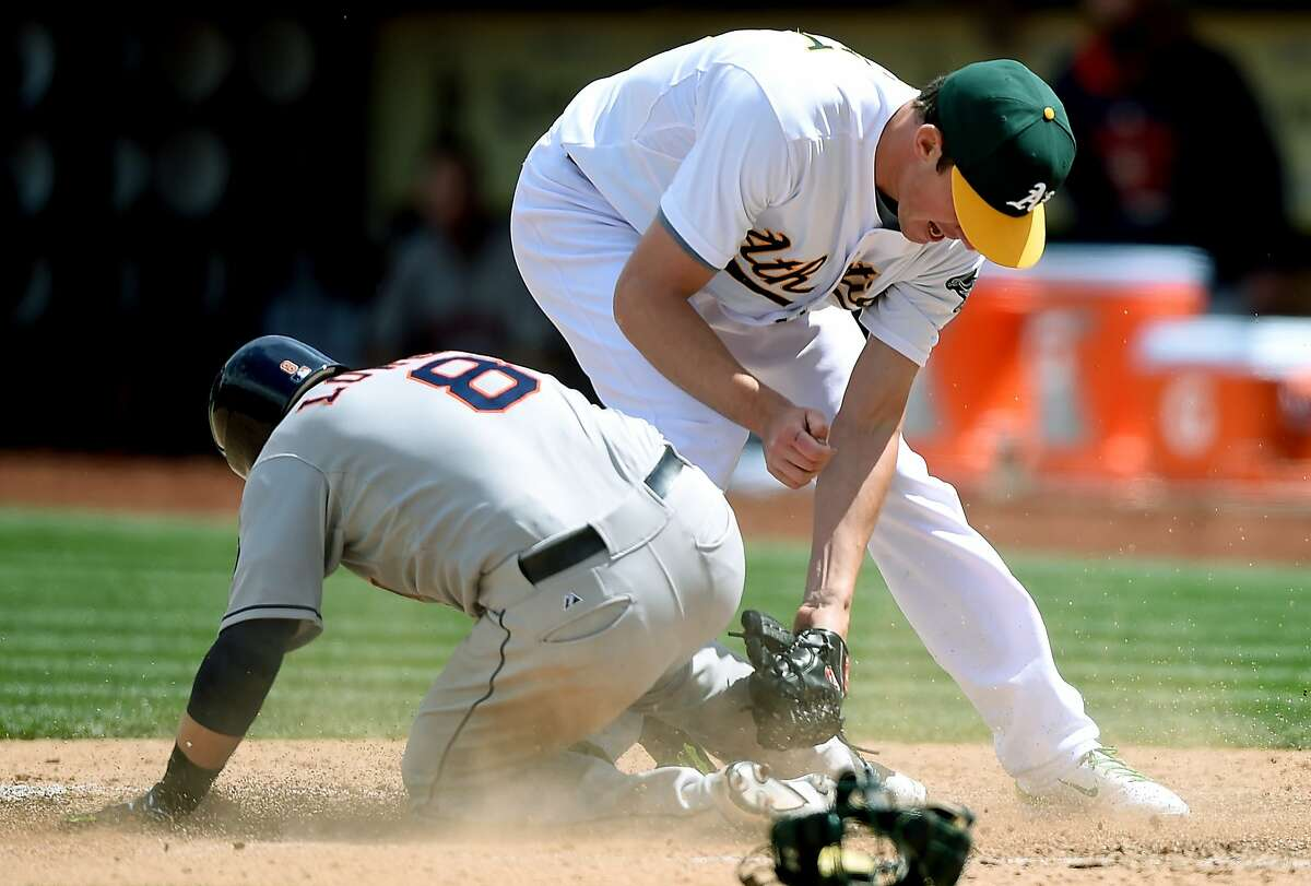 Jed Lowrie #8 of the Houston Astros scores on a wild pitch beating the tag of Chris Bassitt #40 of the Oakland Athletics in the top of the fifth inning at O.co Coliseum on April 25, 2015 in Oakland, California. The Astros won the game 9-3.