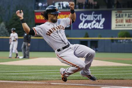 San Francisco Giants' Angel Pagan slides safely across home plate to score on an RBI-double hit by Buster Posey against the Colorado Rockies in the first inning of a baseball game Saturday, April 25, 2015, in Denver. (AP Photo/David Zalubowski)