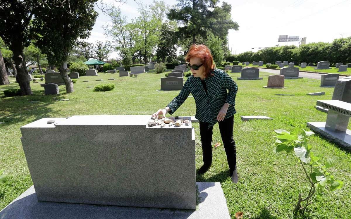 Bari Brochstein-Ruggeri places a rock from Israel on the family headstone at the gravesite of her daughter, Jennifer Marissa Ruggeri, at Beth Yeshurun Cemetery in Houston.