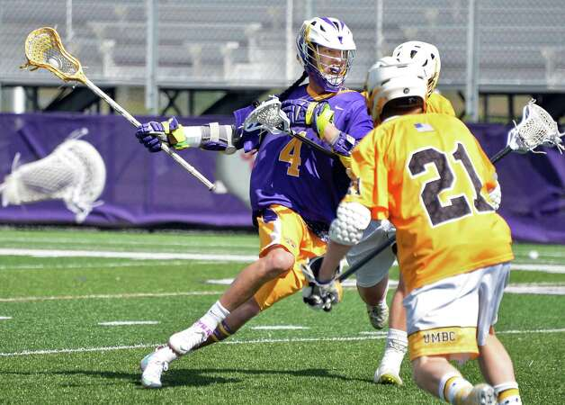 UAlbany's #4 Lyle Thompson, left, charges into Maryland-Baltimore County defenders during Saturday's game at Bob Ford Field April 25, 2015 in Albany, NY.  (John Carl D'Annibale / Times Union) Photo: John Carl D'Annibale / 00031590A