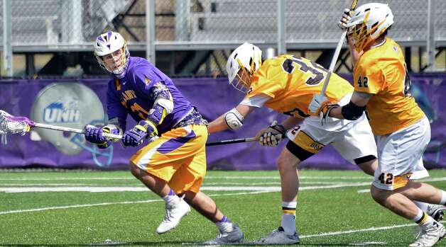 UAlbany's #21 Seth Oakes, left, gets away from Maryland-Baltimore County defenders #32 Steve Windsor and #42 Ian Gray, right, during Saturday's game at Bob Ford Field April 25, 2015 in Albany, NY.  (John Carl D'Annibale / Times Union) Photo: John Carl D'Annibale / 00031590A