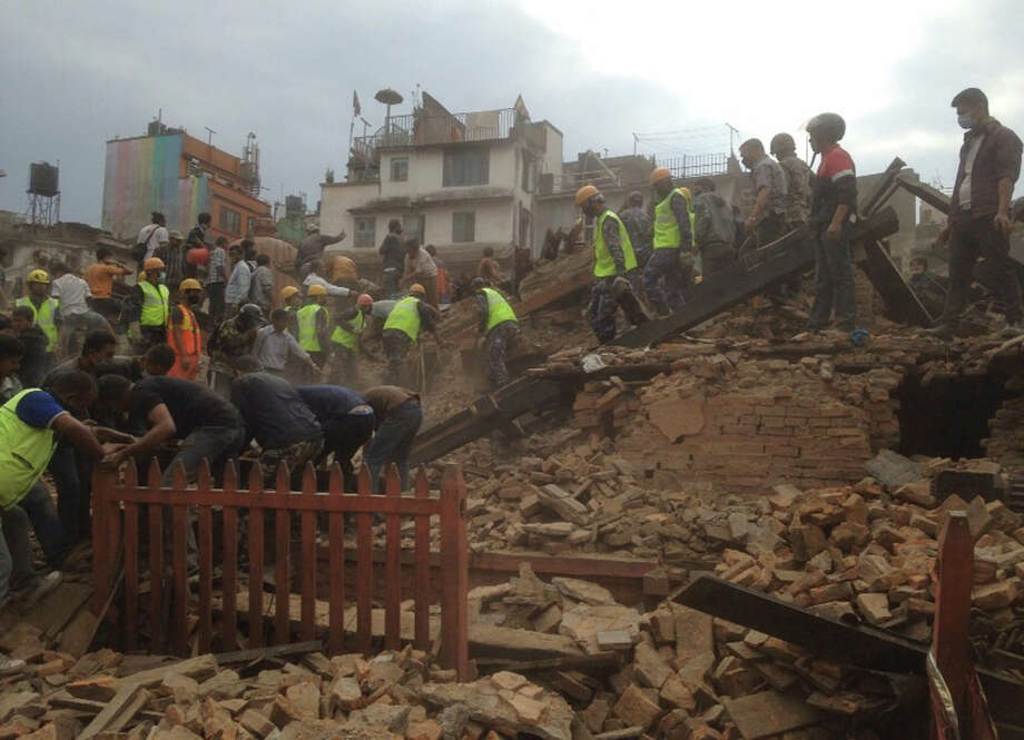 Rescuers clear the debris at Durbar Sqaure after an earthquake in Kathmandu, Nepal, Saturday, April 25, 2015. A strong magnitude-7.9 earthquake shook Nepal's capital and the densely populated Kathmandu Valley before noon Saturday, causing extensive damage with toppled walls and collapsed buildings, officials said. (AP Photo/ Niranjan Shrestha) ORG XMIT: DEL120 Photo: Niranjan Shrestha / AP
