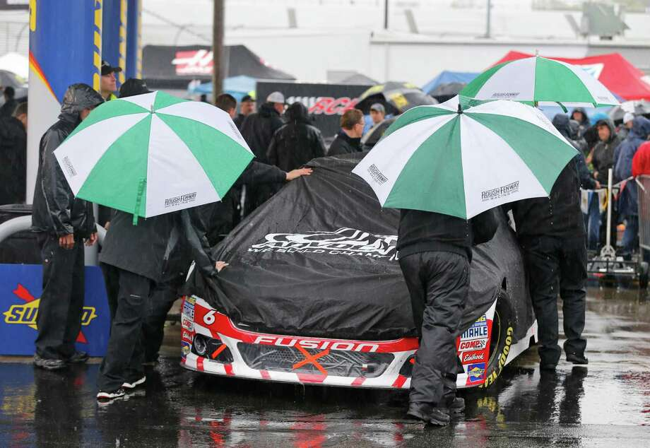 The crew for Trevor Bayne (6) pushes his car to the inspection station as rain falls at Richmond International Raceway in Richmond, Va., Saturday, April 25, 2015. The NASCAR Sprint Cup series races was postponed until Sunday. (AP Photo/Steve Helber) ORG XMIT: VASH103 Photo: Steve Helber / AP
