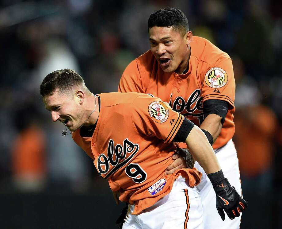 Baltimore Orioles' David Lough, left, is chased by teammate Everth Cabrera after hitting a walkoff home run against Boston Red Sox in the 10th inning of a baseball game, Saturday, April 25, 2015, in Baltimore. The Orioles won 5-4. (AP Photo/Gail Burton) ORG XMIT: MDGB116 Photo: Gail Burton / FR4095 AP