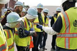 Tour guide and Material Testing Aid Jonathan Smith encourage visitors to sniff the bio solid ball that doesn't smell bad at the San Francisco Southeast Treatment sewage plant in San Francisco, Calif., Saturday April 25, 2015.