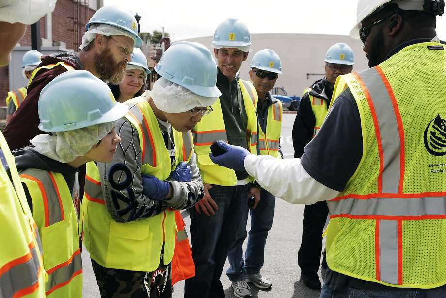 Tour guide and Material Testing Aid Jonathan Smith encourage visitors to sniff the bio solid ball that doesn't smell bad at the San Francisco Southeast Treatment sewage plant in San Francisco, Calif., Saturday April 25, 2015. Photo: Sophia Germer, The Chronicle