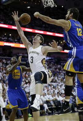 New Orleans Pelicans center Omer Asik (3) is blocked by Golden State Warriors center Andrew Bogut (12) while driving to the basket past Warriors forward Harrison Barnes (40) during the second half of Game 4 of a first-round NBA basketball playoff series in New Orleans, Saturday, April 25, 2015. The Warriors won 109-98 to sweep the series. (AP Photo/Gerald Herbert)