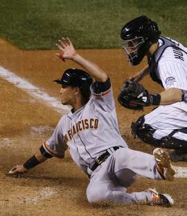 San Francisco Giants' Nori Aoki, left, slides safely across home plate with the go-ahead run next to Colorado Rockies catcher Nick Hundley (4) during the 11th inning of a baseball game Saturday, April 25, 2015, in Denver. The Giants won 5-4 in 11 innings.(AP Photo/David Zalubowski)