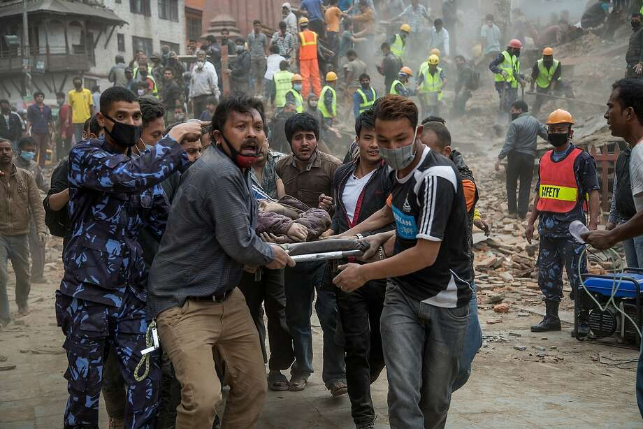 Emergency rescue workers carry a victim on a stretcher after Dharara tower collapsed on April 25, 2015 in Kathmandu, Nepal. More than 100 people have died as tremors hit Nepal after an earthquake measuring 7.9 on the Richter scale caused buildings to collapse and avalanches to be triggered in the Himalayas. Authorities have warned that the death toll is likely to be much higher. Photo: Omar Havana