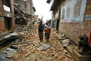 An elderly injured woman is taken home through earthquake debris after treatment in Bhaktapur near Kathmandu, Nepal, Sunday, April 26, 2015. A strong magnitude 7.8 earthquake shook Nepal's capital and the densely populated Kathmandu Valley before noon Saturday, causing extensive damage with toppled walls and collapsed buildings, officials said.