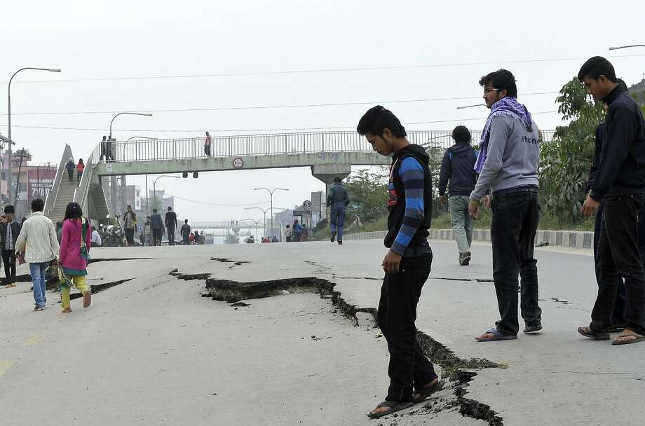 Nepalese residents walk past road damage following an earthquake in Kathmandu on April 26, 2015.   Photo: Prakash Mathema, AFP / Getty Images