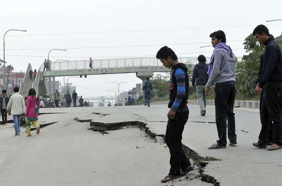 Nepalese residents walk past road damage following an earthquake in Kathmandu on April 26, 2015.  Photo: Prakash Mathema, AFP / Getty Images