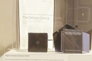 """An exhibit at the Mead Art Museum on the Amherst College campus displays a kit that can be used to build a version of Jonathon Keats' """"millennium camera"""" designed to make an exposure over 100 years Thursday, April 16, 2015, in Amherst, Mass. Keats, a San Francisco-based writer who describes himself as an experimental philosopher and conceptual artist, has designed a camera he plans to perch atop a church-less steeple on the Amherst College campus, hoping the device will chronicle climate change by making a 1,000-year-long photograph of the Holyoke Range in western Massachusetts. (AP Photo/Stephan Savoia)"""