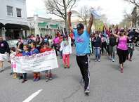 Grand Marshal Eddie Calle, a Zumba instructor, leads the Breast Cancer Alliance Walk for Hope along Mason Street and Greenwich Avenue in Greenwich, Conn. Sunday, April 26, 2015.  More than 500 folks participated in the 10th annual walk to raise money and awareness for breast cancer.