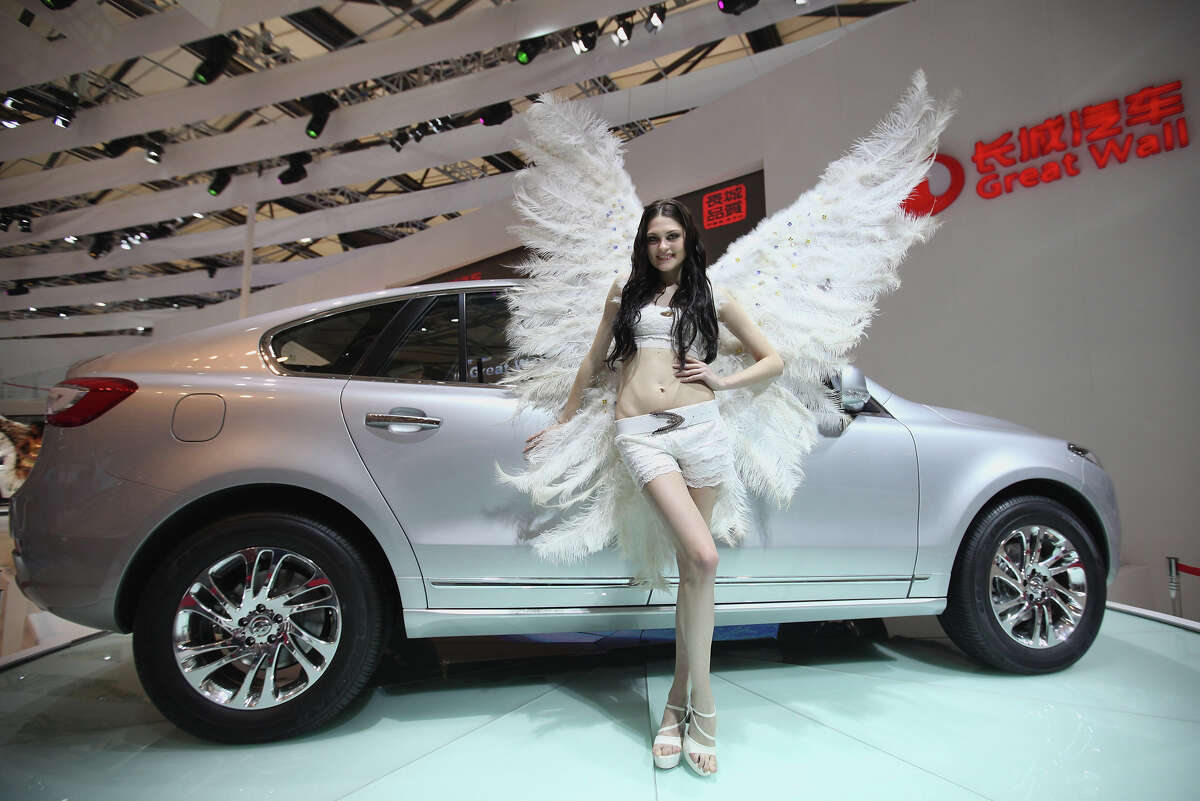 A model poses beside a Great Wall Hover 1F car during the media day of the Shanghai International Automobile Industry Exhibition at Shanghai New International Expo Center on April 20, 2011 in Shanghai, China.