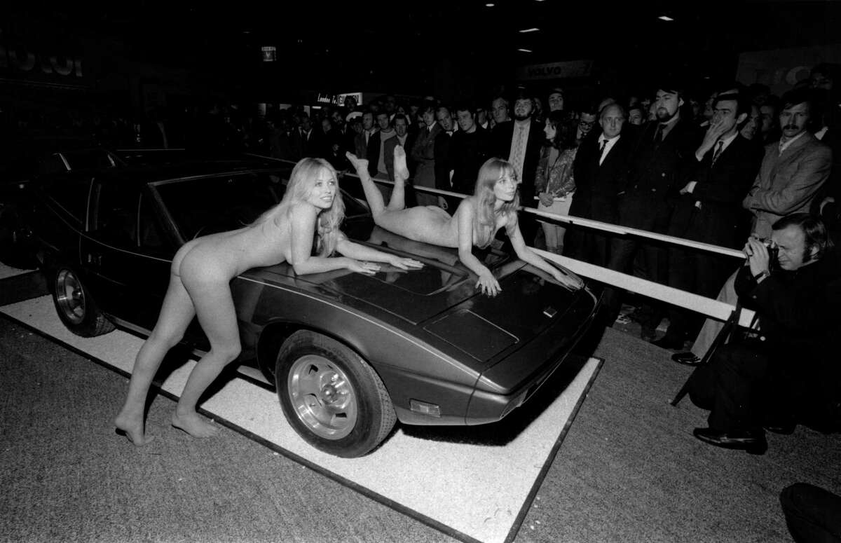 Models Helen Jones and Sue Shaw lying on a car without clothes on at the Motor Show Earls Court.