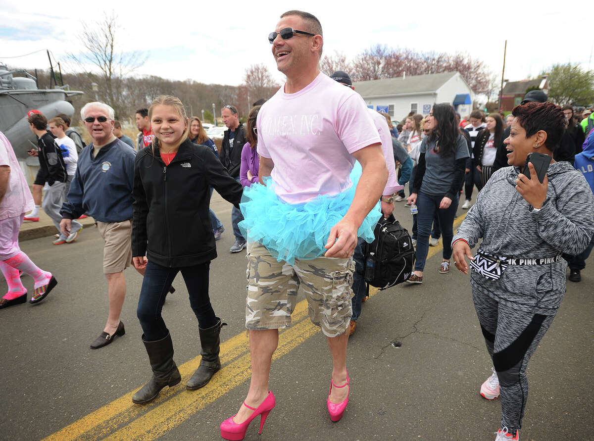 Mike Bakis, of Orange, wears five inch pink heels and a blue tutu for the annual Walk A Mile In Her Shoes event at Lisman Landing on Factory Lane in Milford, Conn. on Sunday, April 26, 2015. With Bakis is daughter Payton, 11, left, who helped him on with his heels. The walk benefits the Rape Crisis Center of Milford.
