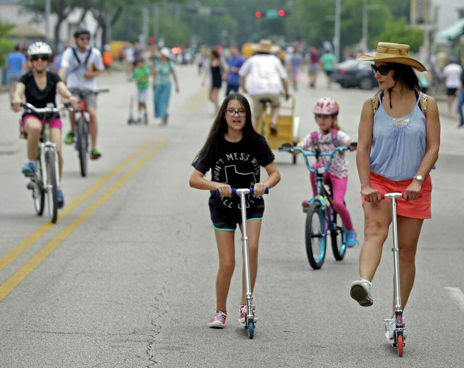 Merrilee Crimmins, 12, center, and her mother, Belinda Crimmins, right, ride scooters along 19th Street during the Sunday Streets in the Heights in 2015. Photo: Melissa Phillip, Houston Chronicle / © 2015  Houston Chronicle