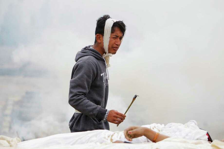 A Nepalese man performs rituals during the cremation of his mother who died in the earthquake in Bhaktapur near Kathmandu, Nepal, Sunday, April 26, 2015. A strong magnitude 7.8 earthquake shook Nepal's capital and the densely populated Kathmandu Valley before noon Saturday, causing extensive damage with toppled walls and collapsed buildings, officials said. Photo: Niranjan Shrestha, AP / AP