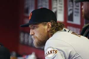 An injured San Francisco Giants' Hunter Pence sits in the dugout prior to a baseball game against the Arizona Diamondbacks Wednesday, April 8, 2015, in Phoenix. (AP Photo/Ross D. Franklin)