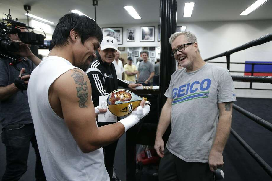 FILE - In this Monday, April 13, 2015, file photo, boxer Manny Pacquiao, left, of the Philippines, and his trainer Freddie Roach share a laugh as they look at a speed bag showing an images of Floyd Mayweather Jr., a gift from lawyer Robert Shapiro, background center, in Los Angeles. Roach has guided Pacquiao to the pinnacle of boxing, yet the most celebrated trainer of his era still rises before dawn and wins his daily fight with Parkinson's disease because he always finds new reasons to live.  (AP Photo/Jae C. Hong, File) Photo: Jae C. Hong, Associated Press