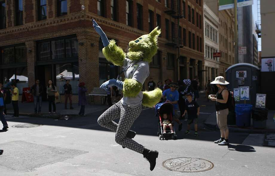 A woman in a furry costume attempts to pop a bubble during the annual How Weird Street Festival on Howard Street in San Francisco, Calif. Sunday, April 26, 2015. Photo: Jessica Christian, The Chronicle